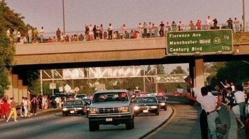 O.J. Simpson en el ford bronco con fans detras