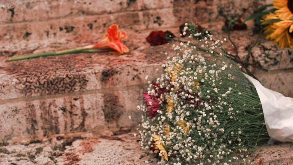 Flores, sobre manchas de sangre, en la escalinata de la mansión Versace.
